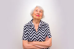 Portrait of a dreaming senior woman sitting with closed eyes. Over gray background Stock Photography