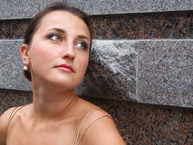 Portrait of a dreaming woman. Portrait of a dreaming young woman in front of a wall Stock Photography