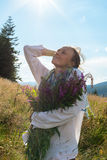 Portrait of  dreaming woman with a bouquet of wildflowers. On the background of a blue sky with sunrays Stock Photo