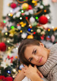 Portrait of dreaming woman near Christmas tree Royalty Free Stock Photography