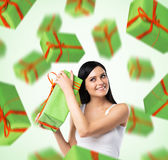 A portrait of dreaming woman who imagines green gift boxes. Light green background stock photography