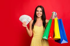 Portrait of dreamy confident excited cheerful attractive woman w. Ith toothy smile carrying many bags with clothes bundle of money in hand wearing yellow Stock Images
