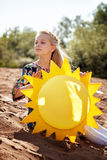 Portrait of dreamy girl posing with paper sun Stock Photos