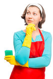 Portrait of a dreamy housewife in apron with sponge Royalty Free Stock Photography