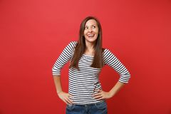 Portrait of dreamy pretty young woman in striped clothes looking up, standing with arms akimbo isolated on bright red. Wall background. People sincere emotions royalty free stock photography