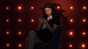 Happy young woman standing by a lit wall using smartphone. Concept: happy or good news. Young woman in hat against. Portrait of dreamy woman in black dress and stock video footage