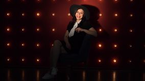 Young woman in hat against illuminated wall. Portrait of dreamy woman in black dress and hat sitting on background of illuminated wall and looking at camera stock video footage