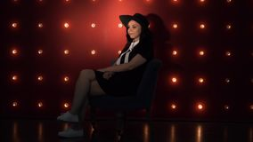 Young woman in hat against illuminated wall. Portrait of dreamy woman in black dress and hat sitting on background of illuminated wall and looking at camera stock video