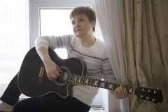 Portrait of dreamy woman with guitar near window at home. Close up Royalty Free Stock Image