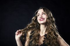 Portrait of a smiling young girl in a lace dress on a black background stock photography