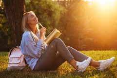 Portrait of a dreamy young girl sitting on a grass. At the park, reading a book, taking notes Stock Photo