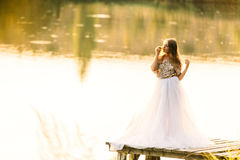 Portrait  in a dress at sunset near a lake. Portrait of a beautiful girl in a dress at sunset near a lake Royalty Free Stock Images