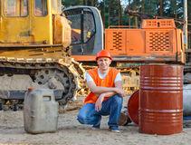 Portrait of driver  construction equipment. Sitting near  fuel drums Stock Images