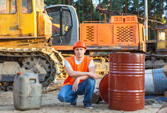 Portrait of driver  construction equipment. Sitting near  fuel drums Stock Image