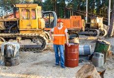 Portrait of driver  construction equipment. Sitting near  fuel drums Stock Photos