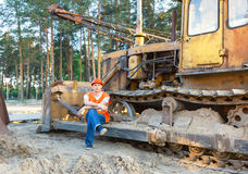 Portrait of driver  construction equipment. Sitting near  fuel drums Royalty Free Stock Images