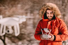 Portrait of drone operator flying quadcopter in winter. Time stock photos