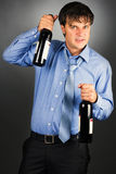 Portrait of a drunk businessman holding two bottles Stock Photo