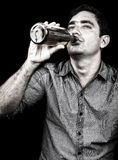 Portrait of a drunk man drinking from a liquor bottle Stock Photography