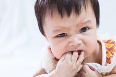 Portrait du bébé asiatique mignon suçant ses doigts dans la bouche photo stock