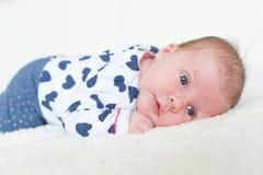 Portrait du bébé aux yeux bleus de 1 mois se trouvant sur le ventre Photographie stock libre de droits