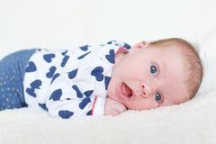 Portrait du bébé aux yeux bleus heureux (1 mois) se trouvant sur le ventre Images stock