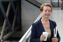 Portrait du banlieusard attirant de femme d'affaires mûres souriant dans le train, l'aéroport ou la station de métro classique da Photographie stock libre de droits