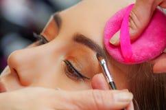Portrait du beau visage de la jeune femme obtenant le maquillage L'artiste applique le fard à paupières sur son sourcil utilisant photo libre de droits