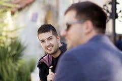 Portrait du bel homme de sourire s'asseyant sur la rue Photo libre de droits