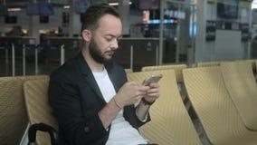 Portrait du blogger de voyage de jeunes, qui écrit un courrier dans les réseaux sociaux dans l'aéroport clips vidéos
