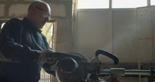 Portrait du charpentier caucasien masculin coupant le bois avec la scie à tronçonner dans la fabrication banque de vidéos