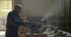 Portrait du charpentier caucasien masculin découpant le bois avec la scie à tronçonner dans de petites places dans la fabrication clips vidéos