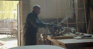 Portrait du charpentier caucasien masculin découpant le bois avec la scie à tronçonner dans la fabrication banque de vidéos