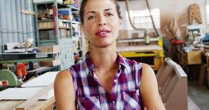 Portrait du charpentier féminin attirant se tenant avec des bras croisés banque de vidéos