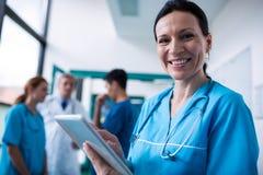 Portrait du chirurgien de sourire à l'aide du comprimé numérique dans le couloir Image stock