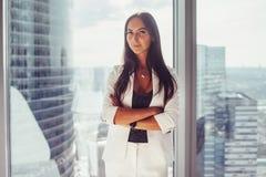 Portrait du costume formel blanc de port de dame élégante d'affaires tenant la fenêtre proche regardant l'appareil-photo Photo stock