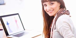 Portrait du couturier féminin attirant s'asseyant au bureau Photographie stock