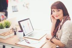 Portrait du couturier féminin attirant s'asseyant au bureau Couturier féminin Image stock