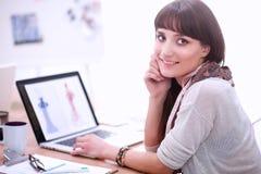 Portrait du couturier féminin attirant s'asseyant au bureau Photo libre de droits