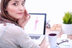 Portrait du couturier féminin attirant s'asseyant au bureau Photographie stock libre de droits