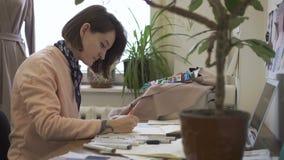 Portrait du couturier féminin, qui travaille au croquis du nouveau modèle dans son studio lumineux banque de vidéos