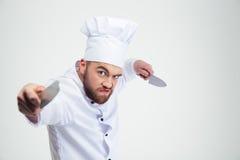 Portrait du cuisinier fâché de chef tenant des couteaux Images stock
