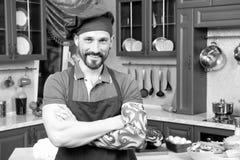 Portrait du cuisinier tatoué barbu positif maintenant des bras croisés photographie stock libre de droits