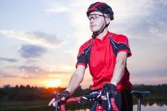 Portrait du cycliste caucasien masculin fait l'heure d'or de coucher du soleil Images stock