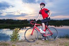 Portrait du cycliste masculin avec son vélo de route posant dehors Photo libre de droits