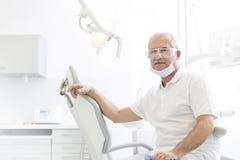 Portrait du dentiste supérieur sûr s'asseyant sur la chaise à la clinique dentaire photographie stock libre de droits