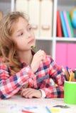 Portrait du dessin réfléchi de petite fille à sa pièce image stock
