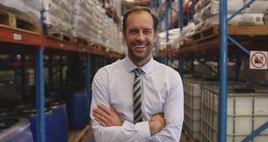 Portrait du directeur masculin souriant dans un entrepôt 4k banque de vidéos
