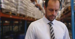Portrait du directeur masculin travaillant dans un entrepôt 4k clips vidéos