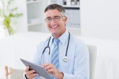Portrait du docteur à l'aide de la tablette Photographie stock libre de droits